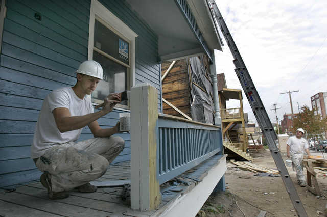 Kyle Blaylock of Polar Bear Painting worked Thursday on the front railing of one of the houses being renovated on Highland Ave. between 18th and 19th streets